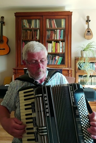 Ian Robertson at home playing the accordion